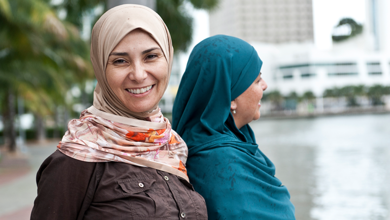 Two women in hijab standing by a river