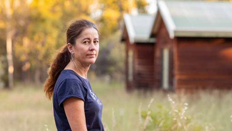 White woman standing in front of small house