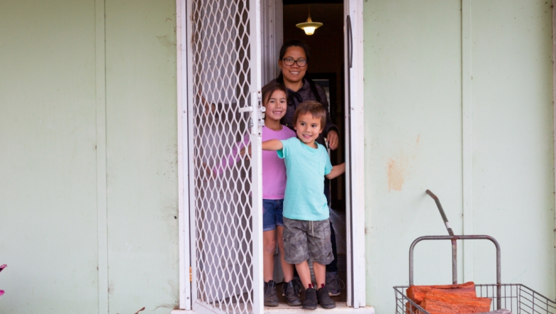Woman of colour standing in her doorway with two children
