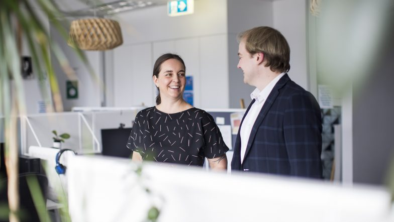 Justice Connect lawyers Samantha Sowerwine and Cameron Laverty stand in the Justice Connect office talking to one another.